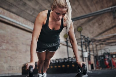 Fit young woman weight training on a gym floor