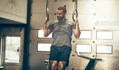 Muscular young man working out on rings at the gym