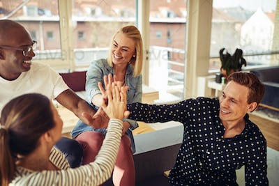 Diverse business colleagues high fiving together in an office
