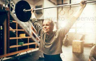 Smiling woman lifting weights over her head in a gym