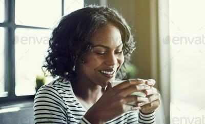Smiling young African woman enjoying a fresh cup of coffee