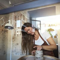 Female artisan creatively sculpting a vase in her pottery studio