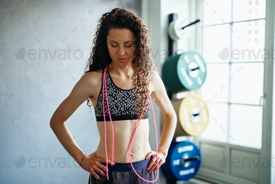 Woman standing with a skipping rope after a gym workout