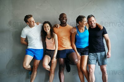 Diverse friends in sportswear laughing together in a gym