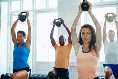 Focused group of people lifting weights together at a gym