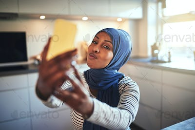 Young Arabic woman making faces while taking selfies at home