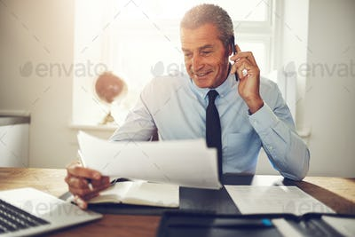 Consultant sitting at a desk discussing documents over the phone
