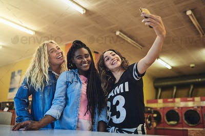 Smiling young friends standing in a laundromat taking selfies together