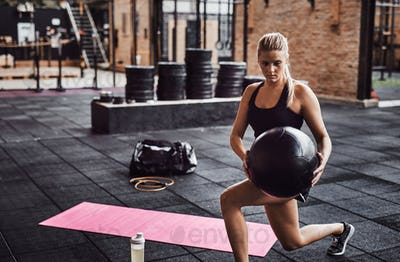 Woman working out with an exercise ball in a gym