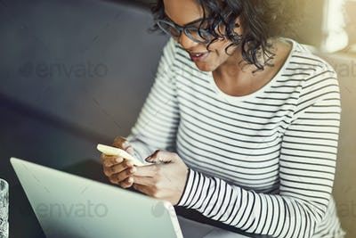 Young African woman using a laptop and reading text messages