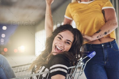 Laughing girlfriends pushing each other in a shopping cart