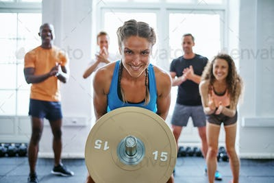 Smiling woman lifting weights with friends clapping in the background