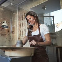 Artisan turning clay on a wheel in her creative workshop