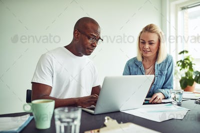 Two businesspeople working online with a laptop together