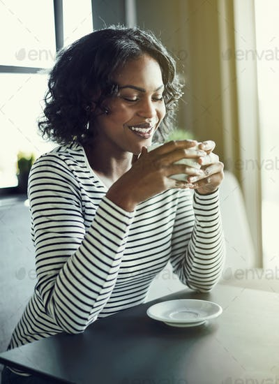 Smiling African woman enjoying the aroma of her fresh coffee