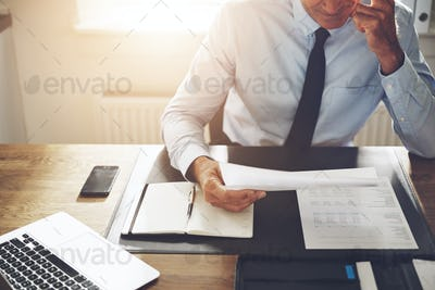 Businessman sitting at an office desk reading through documents
