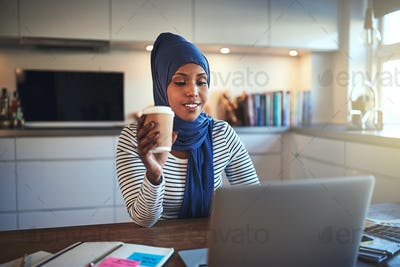 Young Arabic woman drinking coffee and working online at home