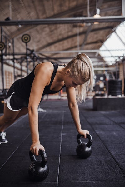 Young woman working out with weights on a gym floor