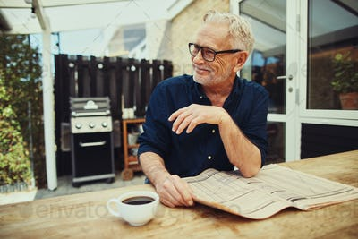 Senior man reading a newspaper outside and drinking coffee