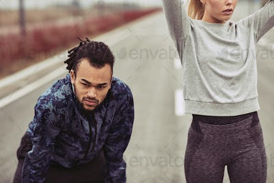 Diverse young couple taking a break from running together