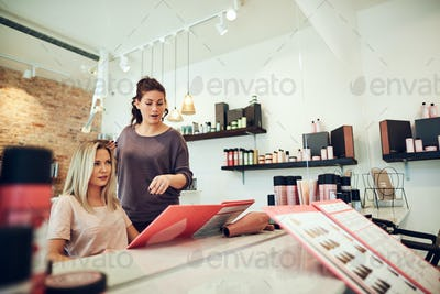 Client and stylist choosing hair dyes during a salon appointment