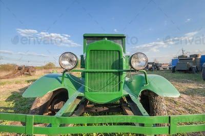 Vintage retro soviet truck green field, front view closeup