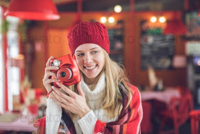 Smiling attractive woman with a red polaroid
