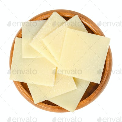 Parmesan cheese slices in wooden bowl over white