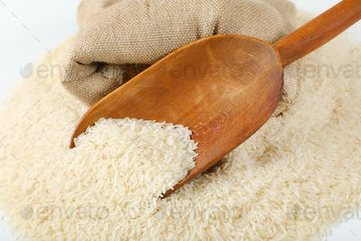 long grained rice, wooden scoop and burlap bag