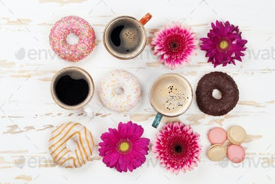 Coffee cups, donuts and gerbera flowers