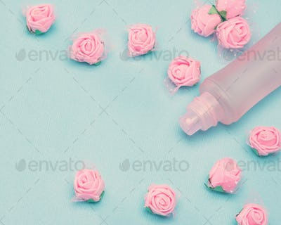Perfume spray bottle and small pink roses