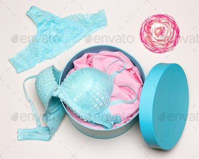 Close-up of open round gift box with blue lingerie set