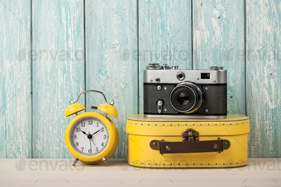 Travel concept with suitcase, film camera and alarm clock