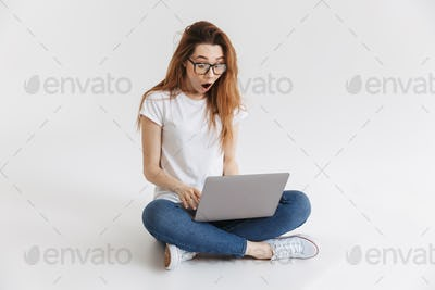 Shocked woman in t-shirt and eyeglasses sitting on the floor