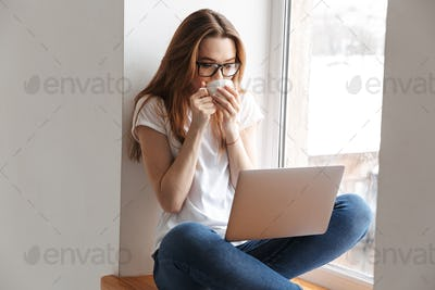 Pretty woman in t-shirt and eyeglasses sitting on windowsill