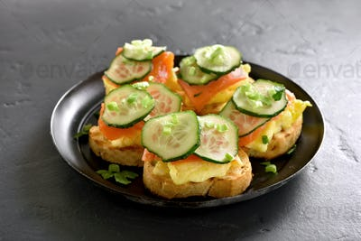 Sandwiches with salmon, scrambled eggs and cucumber