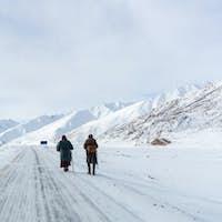 two pilgrims on snow area plateau