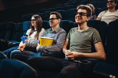 People with popcorn watching movie in cinema