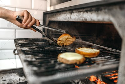 Male cook prepares tasty meat on grill oven