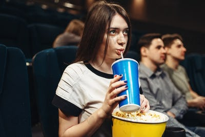 Woman with beverage and popcorn sitting in cinema