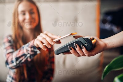 Young woman pay by mobile phone in cafe