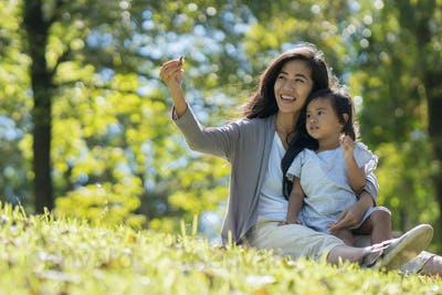 happy young daughter with mom in the park