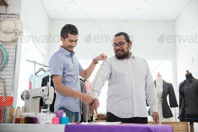 male fashion designer take a measure for clothing