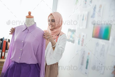 woman tailor working with mannequin