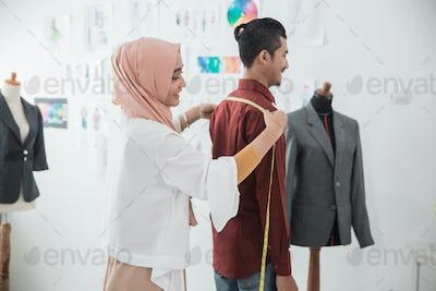 female fashion designer take a measure for clothing