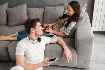 Photo of loving husband and wife in casual clothing resting in l
