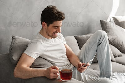 Handsome man in basic t-shirt smiling and holding mobile phone i
