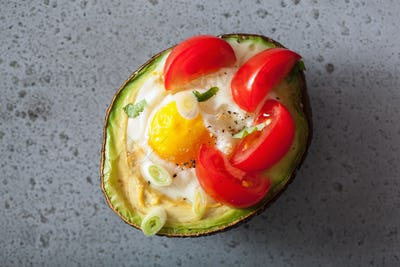 egg baked in avocado with spring onion and tomatoes