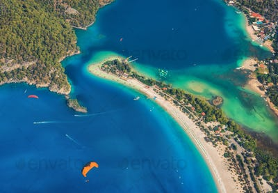 Colorful summer landscape with sea spit, green forest, azure water