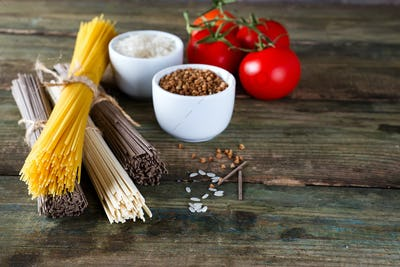 bunch of Italian spaghetti, noodles soba and sommel, bowls with buckwheat and rice with tomato